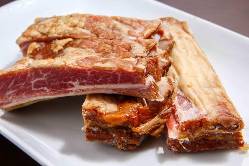 東洋肉店の羊の骨付きスモークベーコンを骨に沿ってカットして皿に盛り付ける
