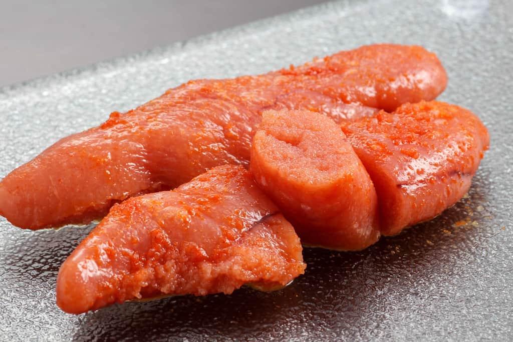 皿の上に乗ったふくやの味の明太子レギュラー、味の明太子をカットして皿にのせる