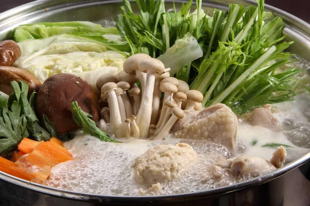 博多華味鳥の水炊き鍋に野菜を入れる