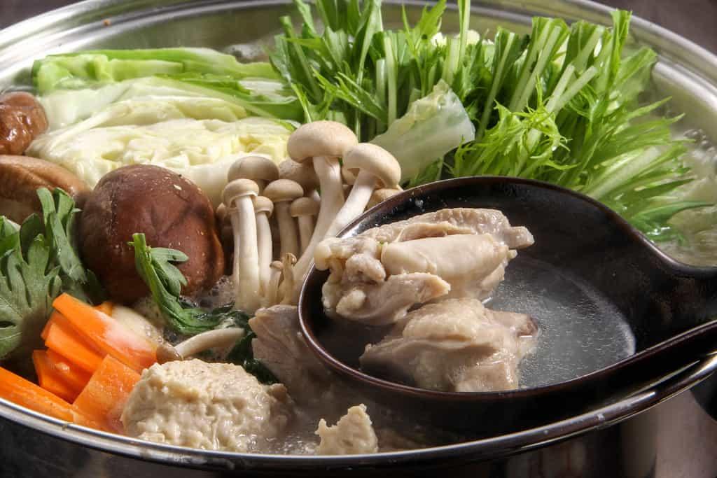 鍋の中で煮立った博多華味鳥の水炊きからレンゲで鶏モモ肉をすくう、水炊きスープの中の華味鳥もも肉