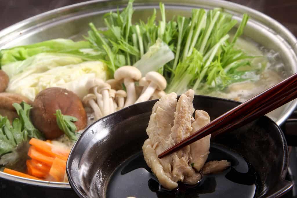 水炊きした華味鳥のモモ肉を特製のポン酢につける