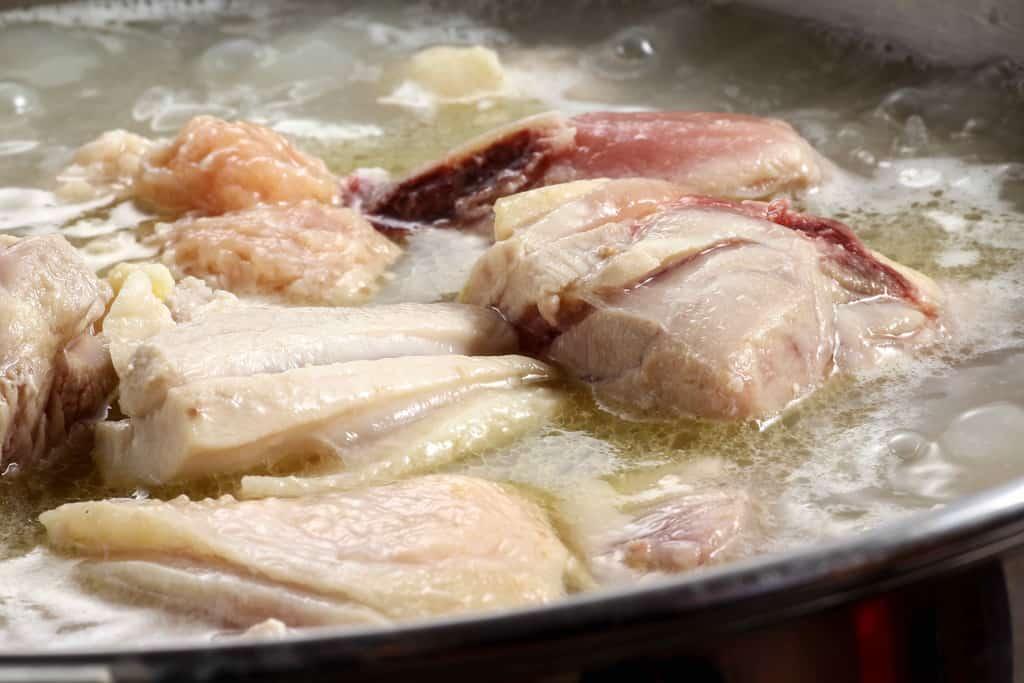 煮立った水炊きスープに浮かぶ華味鳥のモモ肉、博多華味鳥の水炊き