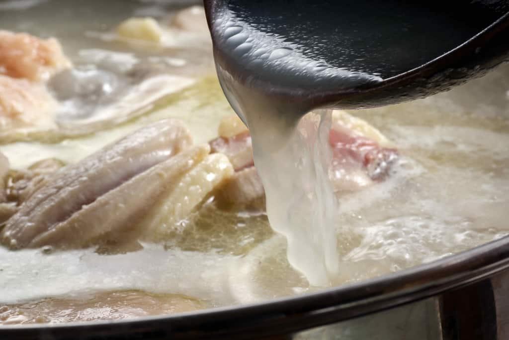 レンゲで博多華味鳥の水炊きスープをすくう、レンゲからこぼれる博多華味鳥の水炊きスープ