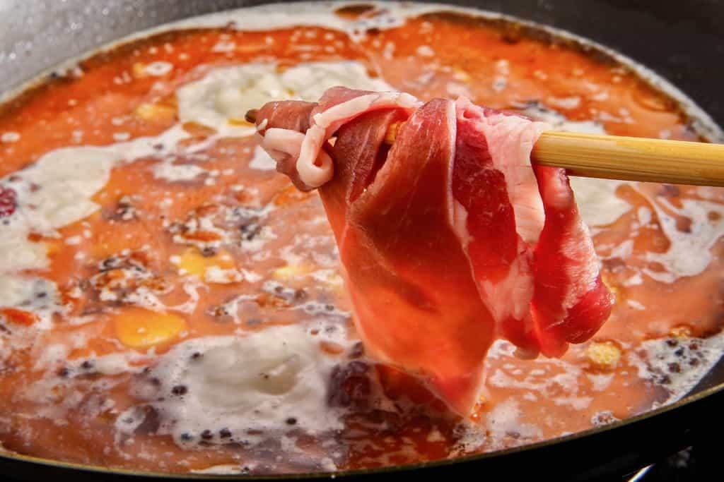 中華鍋の煮立った麻辣スープに東洋肉店のラム肉スライスを入れてしゃぶしゃぶ、火鍋