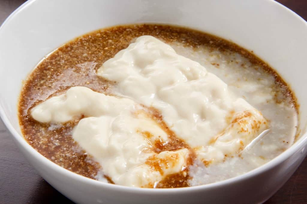 胡麻だれで味わう佐嘉平川屋の温泉湯豆腐、ゴマだれが入った器に湯豆腐を入れる