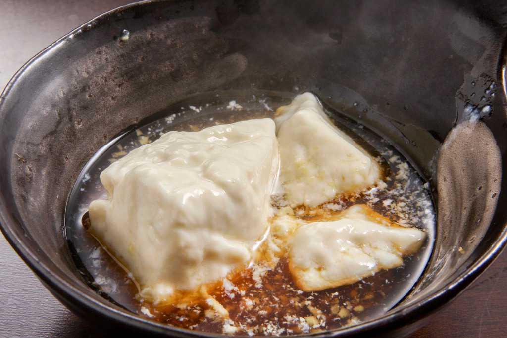 ポン酢で味わう佐嘉平川屋の温泉湯豆腐、ぽん酢の入った器に湯豆腐を入れる