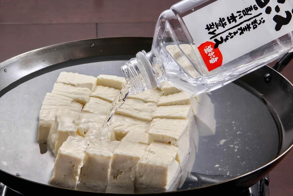 鍋に豆腐を入れ温泉豆腐用の調理水をかける、佐嘉平川屋の嬉野温泉名物の温泉湯豆腐、