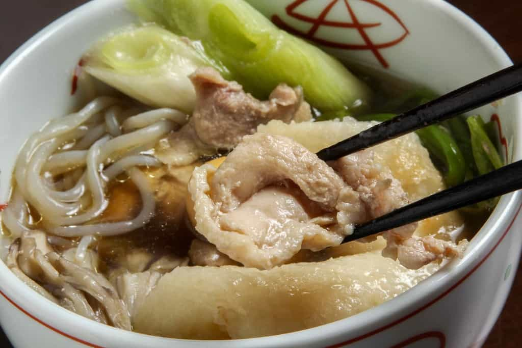 きりたんぽ鍋に入っている比内地鶏のもも肉を箸で持ち上げる