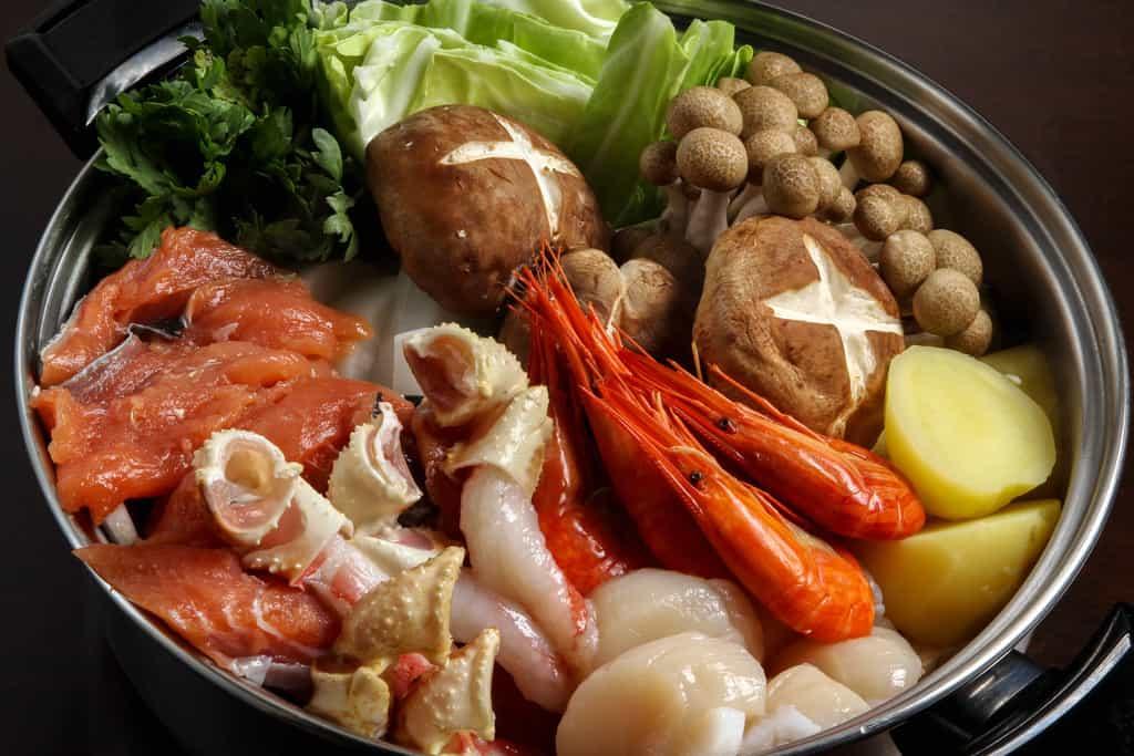 北釧水産の石狩鍋の具材と野菜を鍋に入れる、お取り寄せ石狩鍋