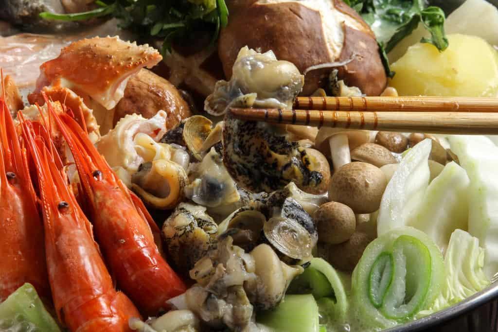 北釧水産の石狩鍋の具材のツブ貝を箸で持つ