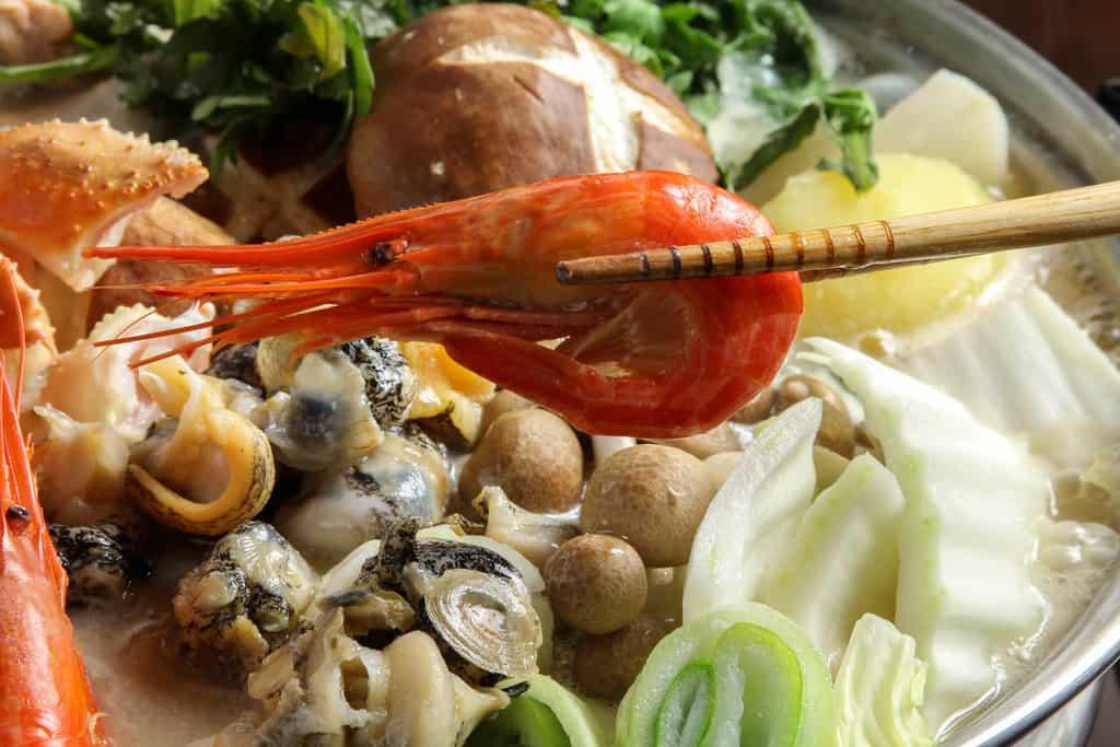北釧水産の石狩鍋の具材の北海シマエビを箸で持つ