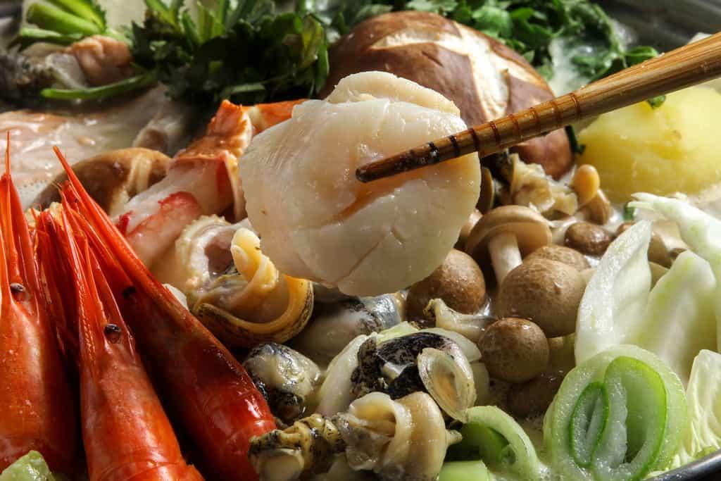 北釧水産の石狩鍋の具材のツブ貝を箸で持つ、帆立が入った石狩鍋