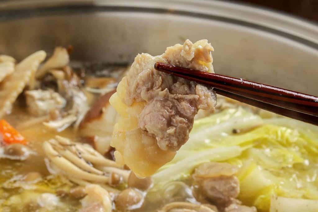石黒農場のほろほろ鳥鍋のもも肉を箸でつまむ、ホロホロ鳥のモモ肉