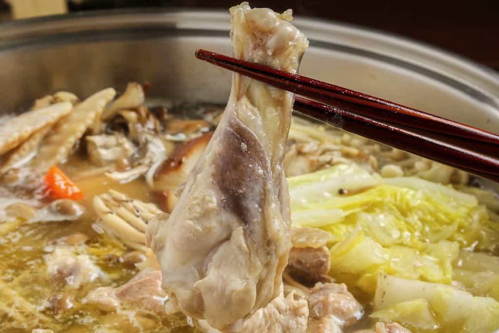 石黒農場のほろほろ鳥鍋の手羽元肉を箸でつまむ、ホロホロ鳥の手羽元