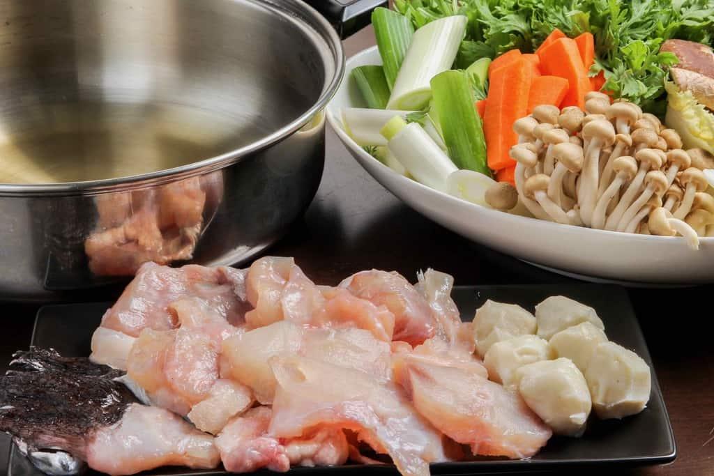 関とらのあんこう鍋セットの鮟鱇の切り身とアラ・つみれ・鍋に入ったスープ・皿に盛った野菜