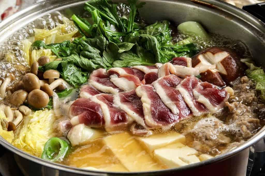 鍋の中で煮立ったアイガモの谷口の但馬鴨鍋、鍋の中で煮立ったスープに合鴨肉を入れる