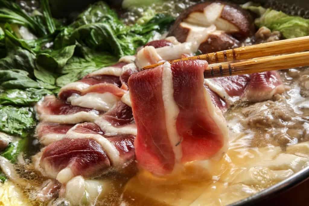 カモ鍋の合鴨ロース肉を箸で持ち上げる、煮立ったかも鍋に但馬鴨ロース肉を入れる
