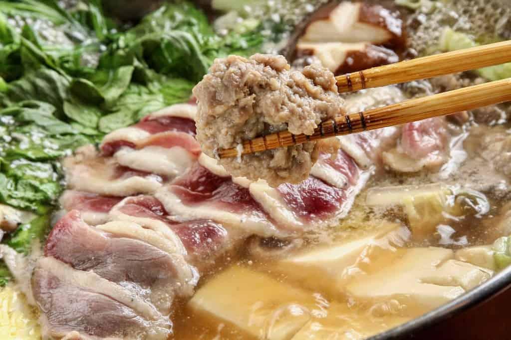 但馬鴨で作ったつくねを箸で持ち上げる、鴨鍋、合鴨料理