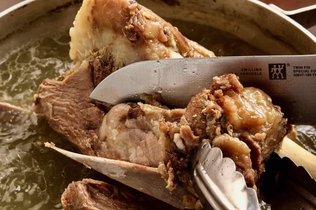 鍋の中で煮込む大きなラム肉の塊を包丁でカットする、モンゴルの羊肉の塩茹で料理、東洋肉店のチャンスンマハ