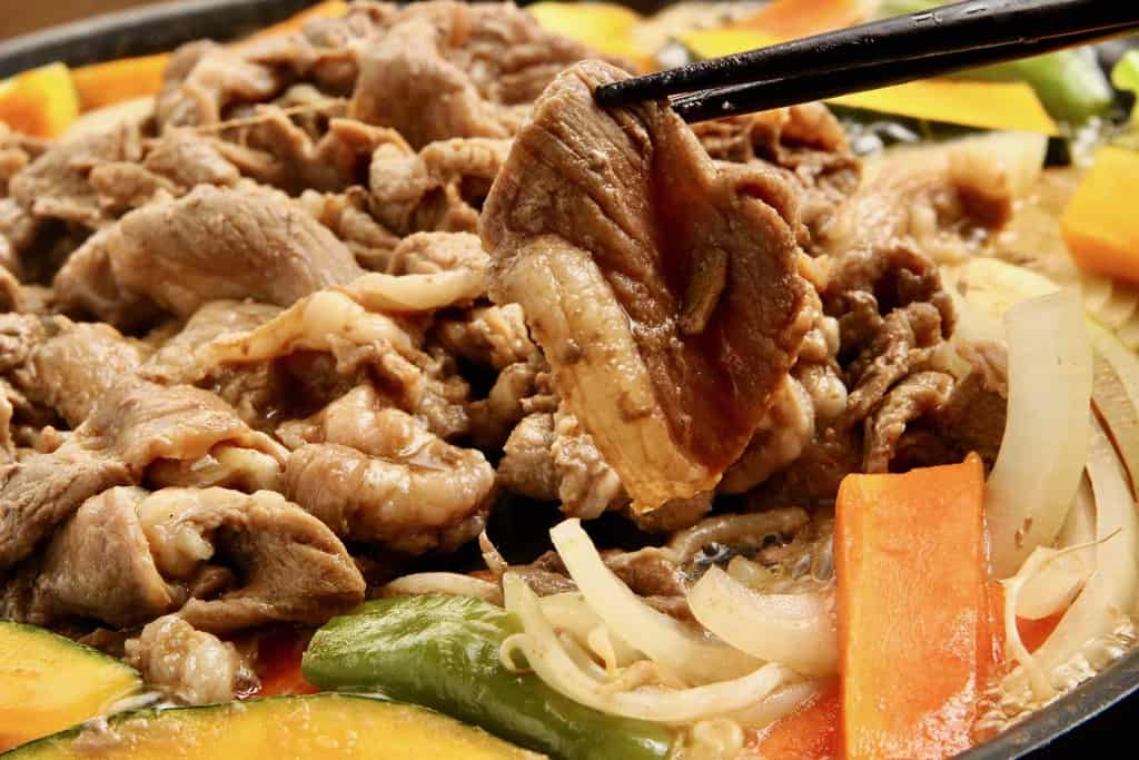 東洋肉店の味付マトンジンギスカン肉1枚を箸で持ち上げる