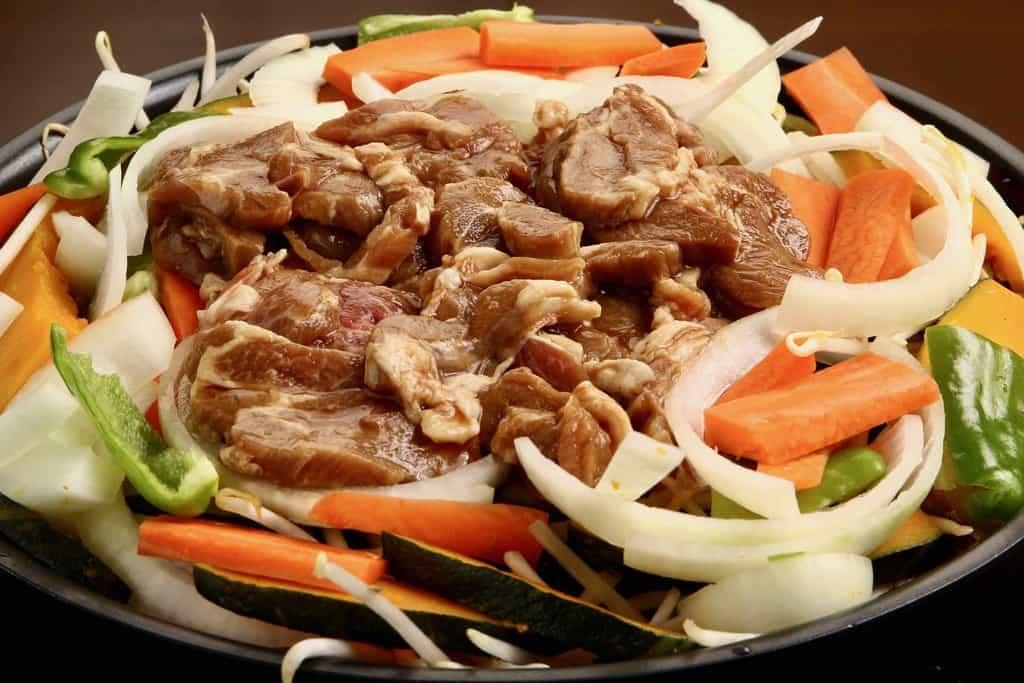 ジンギスカン鍋に山盛りにした東洋肉店の味付きラム肩ロースジンギスカンと玉ねぎ・人参・かぼちゃ・ピーマン・もやし