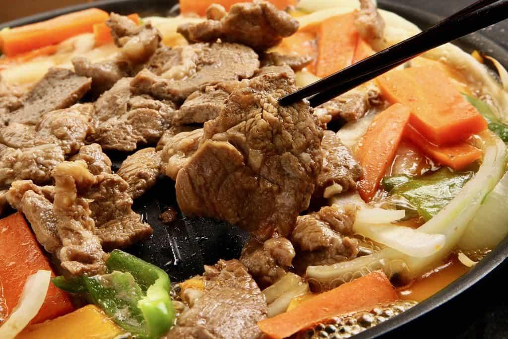 東洋肉店の味付ラム肩ロースジンギスカン肉1枚を箸で持ち上げる