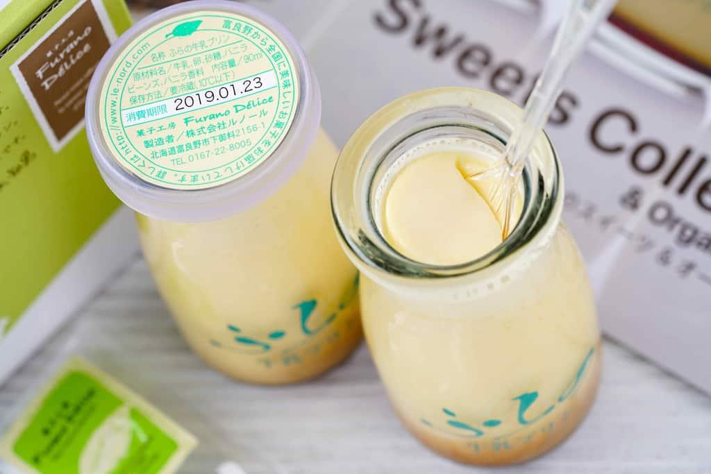 フラノデリスのふらの牛乳プリンの瓶にスプーンを入れる