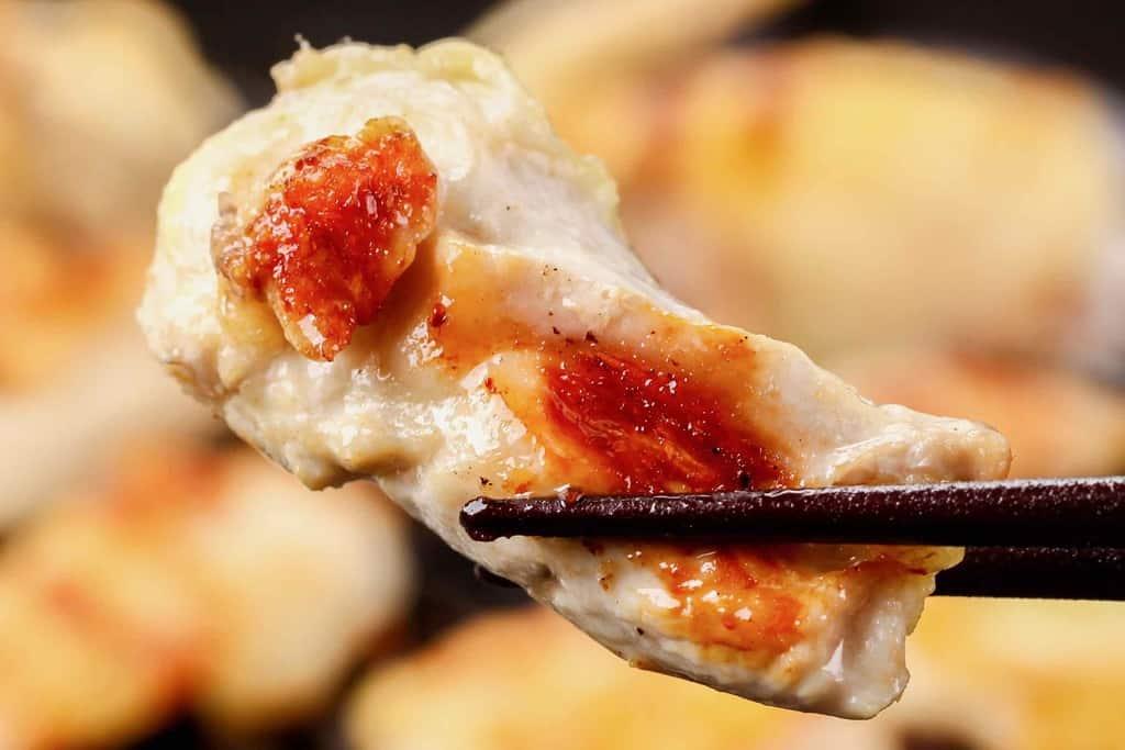 さつま地鶏のムネ肉のグリル、グリルしたさつま地鶏のむね肉を箸でつまむ