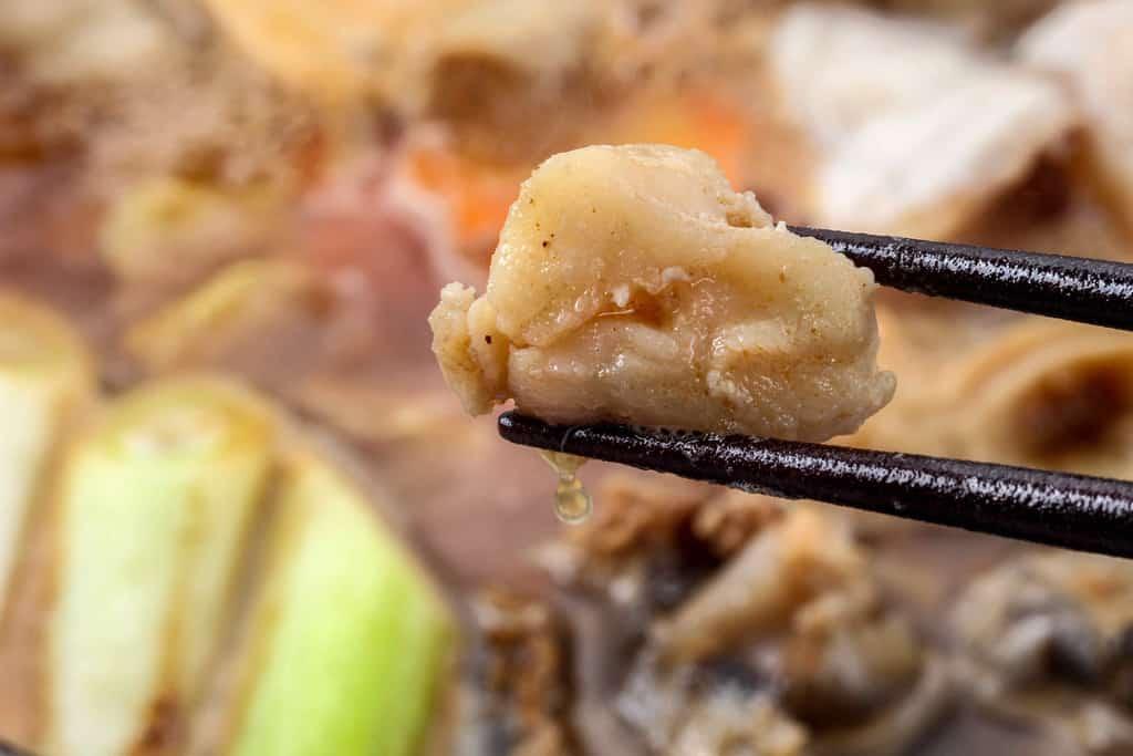 煮立ったあんこう鍋が入った土鍋を背景にあんこうの身をはしで持ち上げる