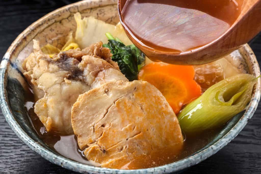 あんこう鍋の具材を器に取り分けてスープを入れる