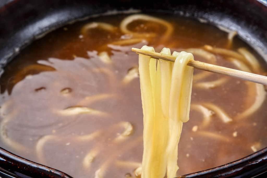 山翠のお取り寄せあんこう鍋の〆うどんを箸で持ち上げる