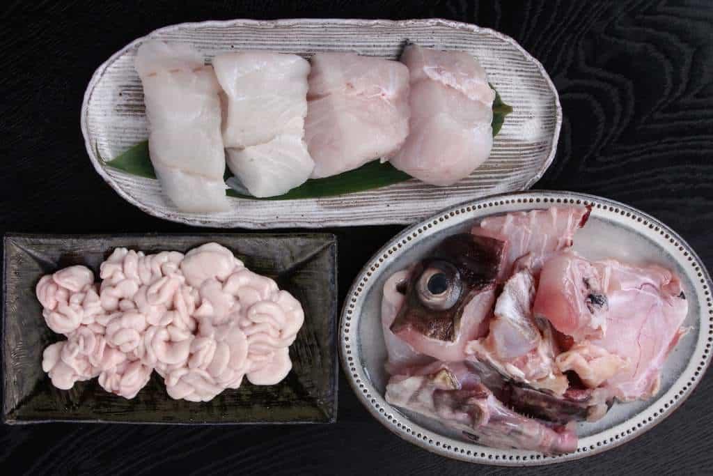 「真鱈の切り身とたち(白子)鍋セット・アラ付き」を容器から取り出して皿に盛り付け