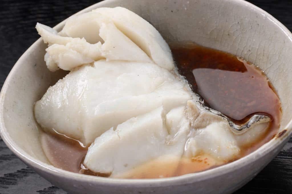 ポン酢の入った器に真鱈の切り身を入れる