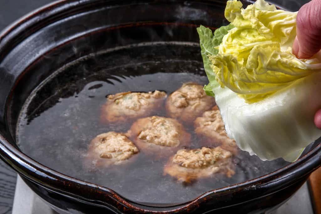 煮立った土鍋の中に白菜を入れる、季節料理門のしょうゆちゃんこに白菜を入れる