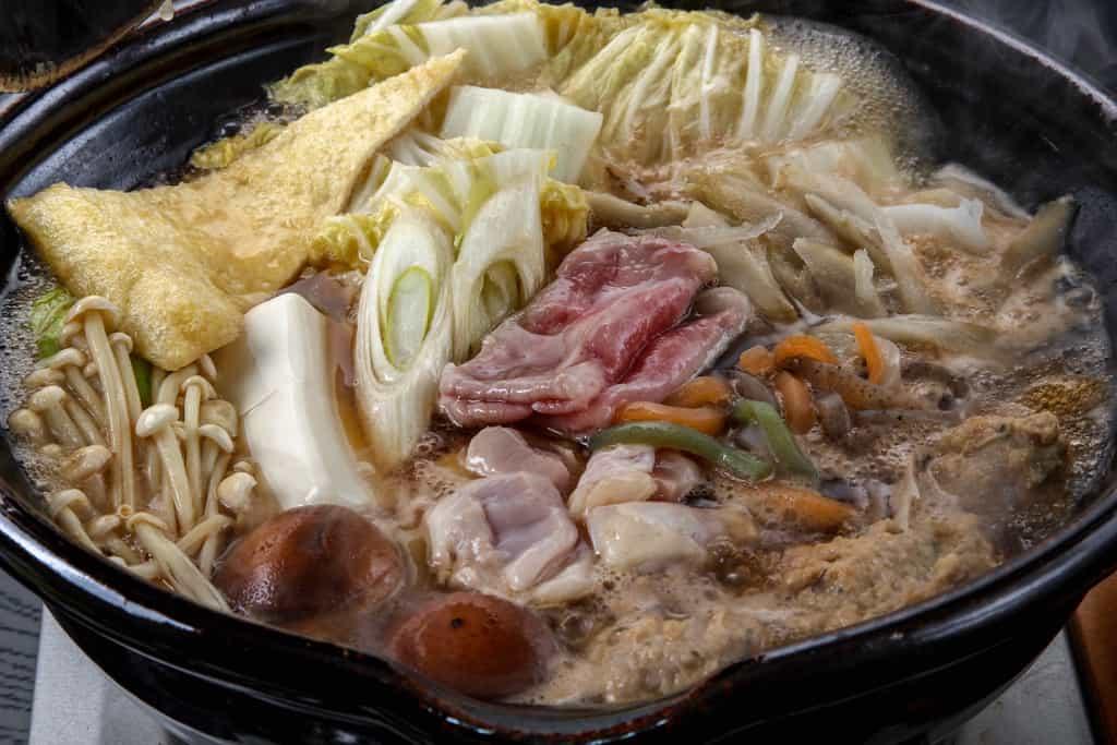 肉や野菜などたくさんの具材が入った土鍋ちゃんこ鍋、季節料理門のしょうゆちゃんこを土鍋で調理