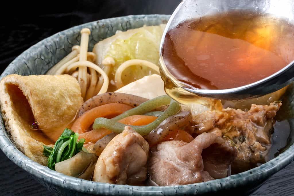 季節料理門のしょうゆちゃんこを小鉢に取り分け、小鉢の中のちゃんこ鍋の具材にスープを入れる