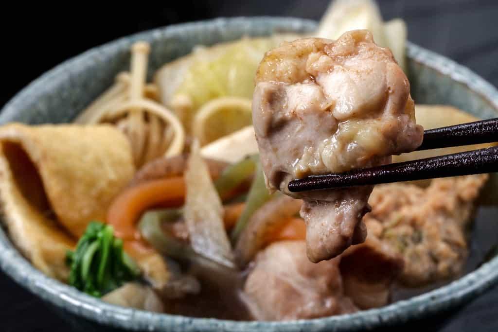 季節料理門のお取り寄せしょうゆちゃんこ鍋の鶏肉を箸で持ち上げる