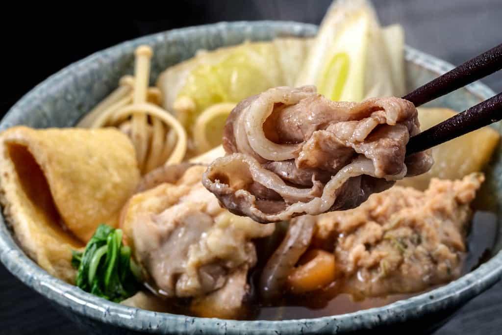 季節料理門の通販しょうゆちゃんこ鍋の豚ロース肉を箸で持ち上げる