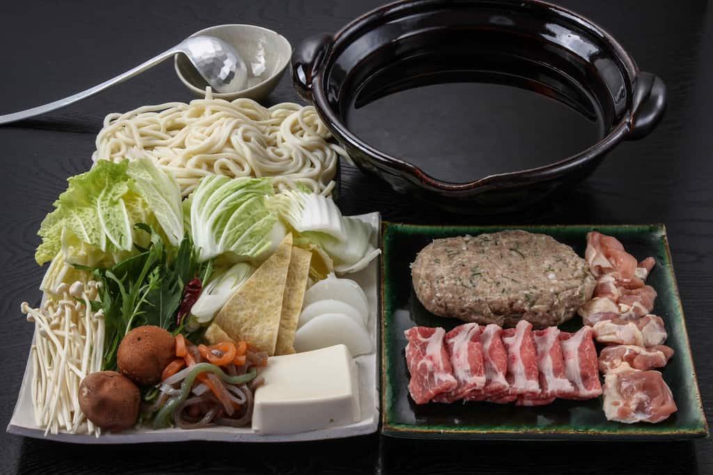 季節料理門の通販しょうゆちゃんこ鍋、土鍋とちゃんこ鍋の具材を皿に並べる、お取り寄せした門のちゃんこ鍋