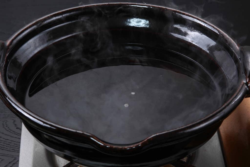 土鍋に入った季節料理門のちゃんこ鍋の自家製醤油スープ
