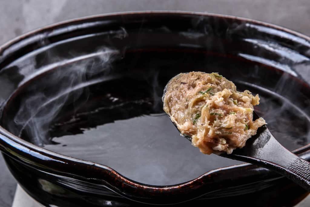 自家製醤油だしの入った土鍋に特製肉団子をレンゲを使って入れる、門の醤油ちゃんこ鍋