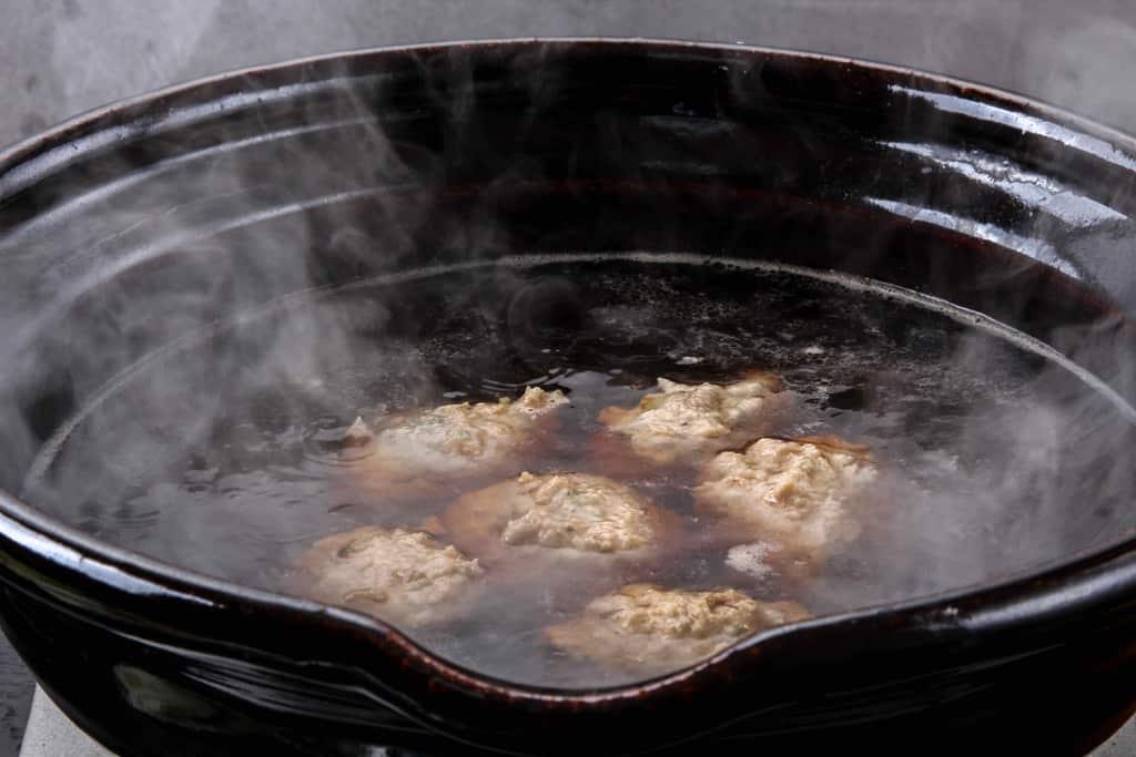 ちゃんこスープが煮立った土鍋、土鍋の中には自家製醤油だしと肉団子