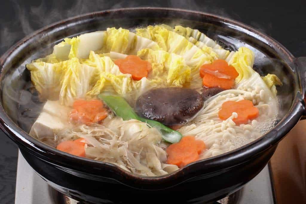 土鍋の蓋を開けると湯けむりが立ち上がった鍋料理