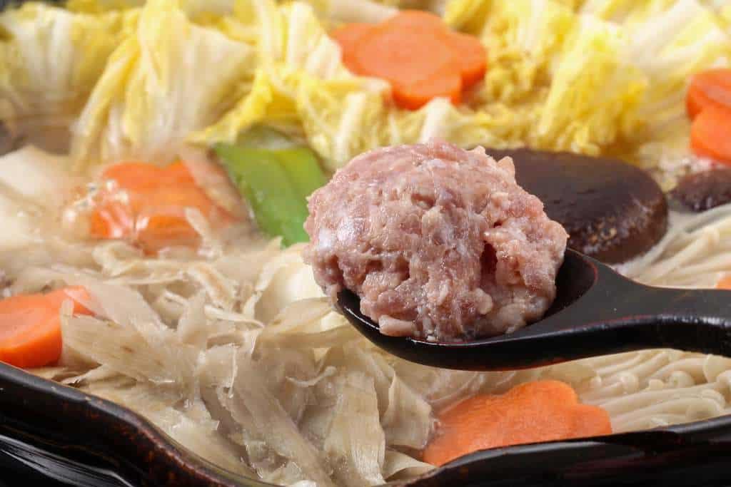 鍋用具材の鴨肉つみれを土鍋に入れる