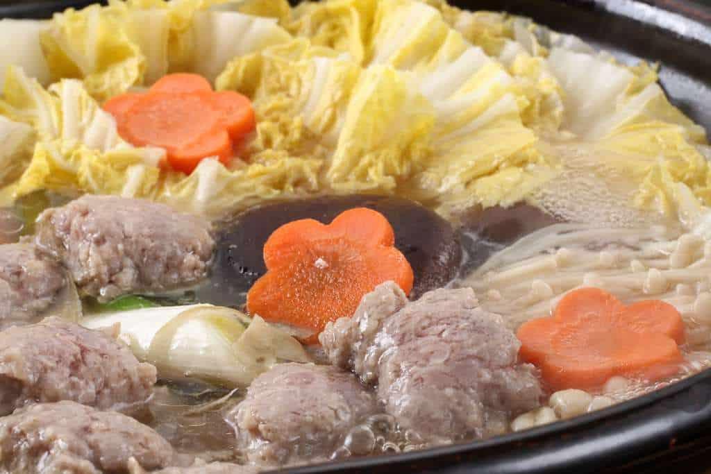 土鍋の中で鴨肉つみれを煮込む
