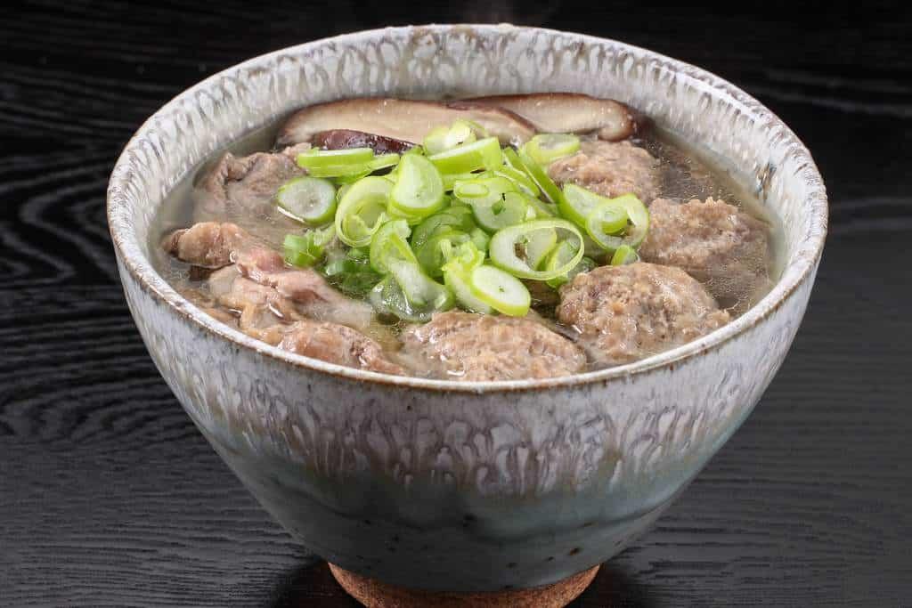 出雲蕎麦をお碗に盛り付けその上に鴨肉と鴨肉つみれとたっぷりのネギ