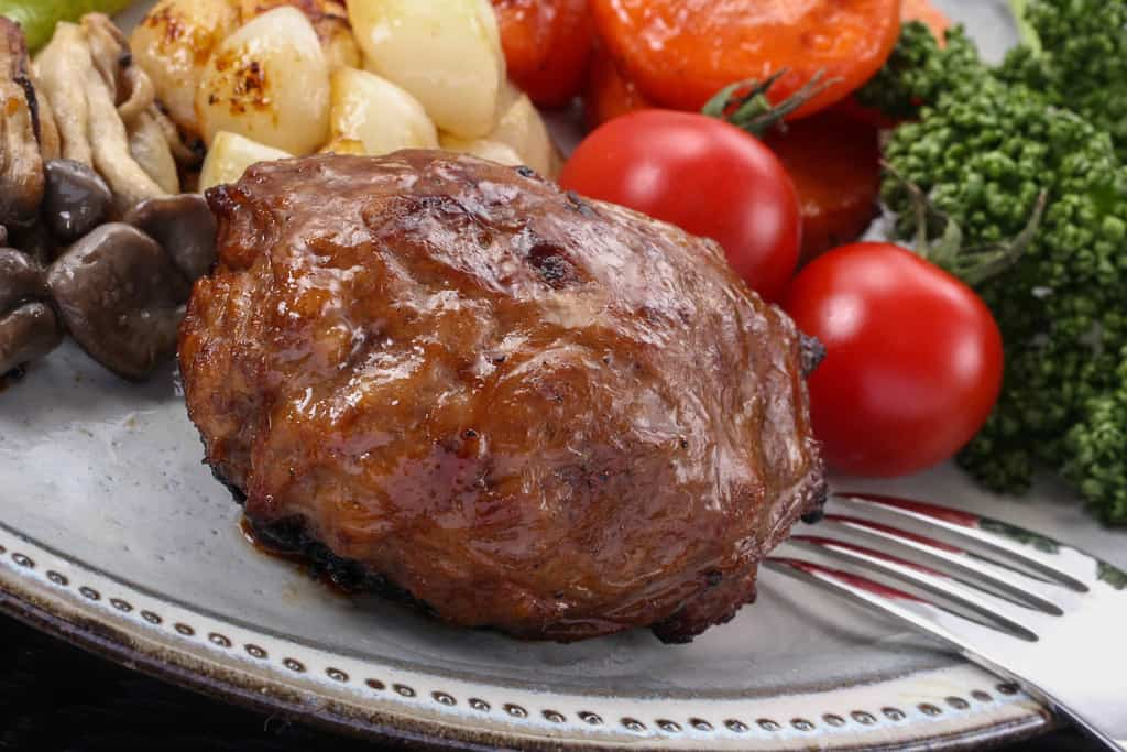 フライパンでソテーし野菜とともに皿に盛り付けた黒毛和牛ハンバーグ