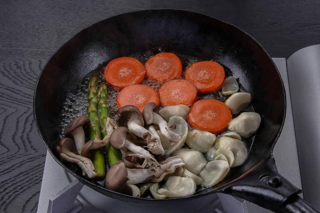 フライパンに敷き詰めた付け合せの野菜に水を加える