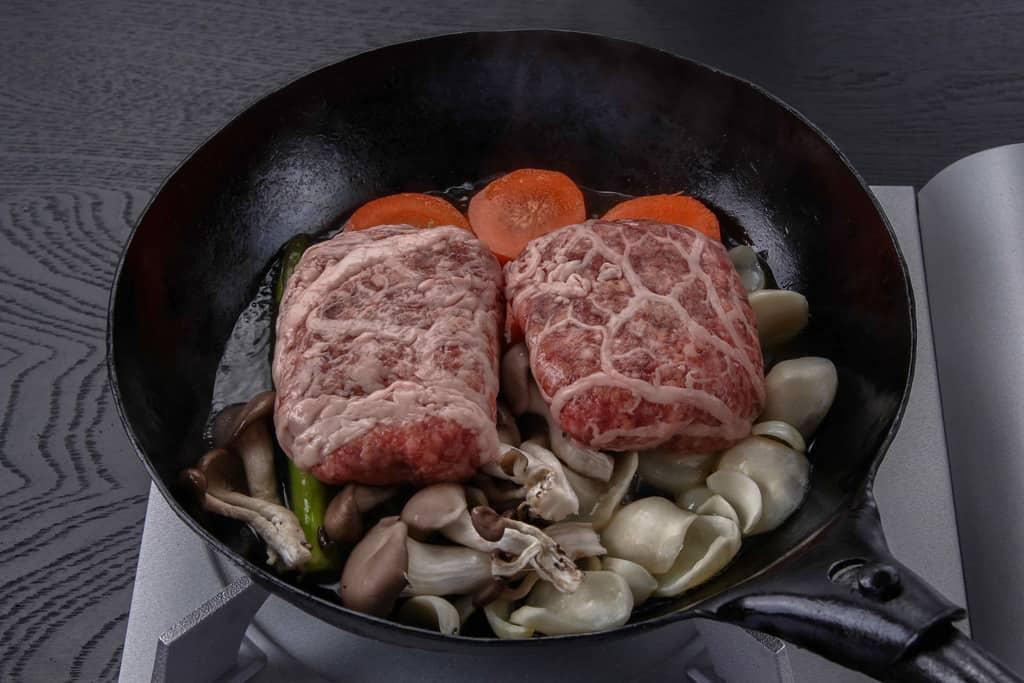 フライパンに敷き詰めた付け合せ野菜の上に黒毛和牛霜降りハンバーグを乗せる