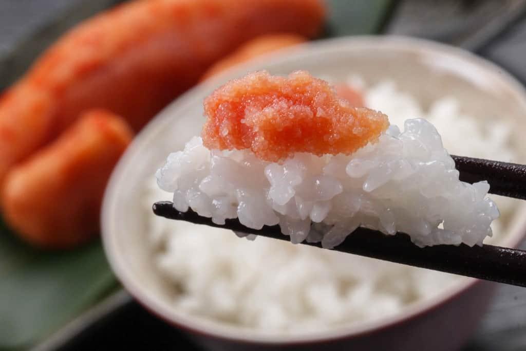 箸でつまんだ白飯の上にのった辛子明太子